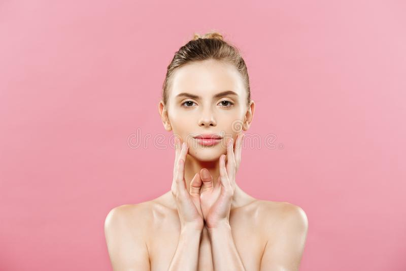 Beauty Spa Concept - Caucasian Woman with perfect face skin Portrait. Beautiful Brunette Spa Girl showing empty copy. Space. Isolated on pink studio background stock image