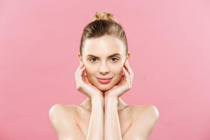 Beauty Spa Concept - Caucasian Woman with perfect face skin Portrait. Beautiful Brunette Spa Girl showing empty copy. Space. Isolated on pink studio background stock images