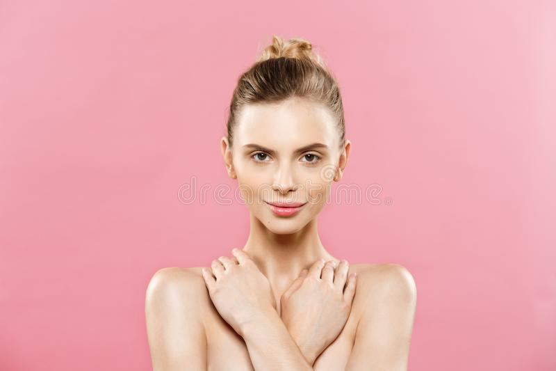 Beauty Spa Concept - Caucasian Woman with perfect face skin Portrait. Beautiful Brunette Spa Girl showing empty copy. Space. Isolated on pink studio background royalty free stock photography