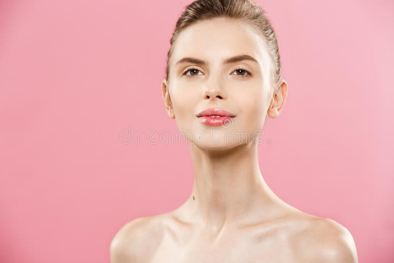 Beauty Spa Concept - Caucasian Woman with perfect face skin Portrait. Beautiful Brunette Spa Girl showing empty copy. Space. Isolated on pink studio background stock photo
