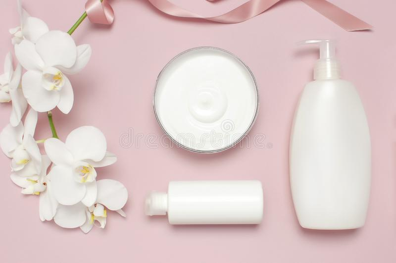 Beauty Spa concept. Opened container with cream, cosmetic bottle containers, white Phalaenopsis orchid flowers on pink background stock photo