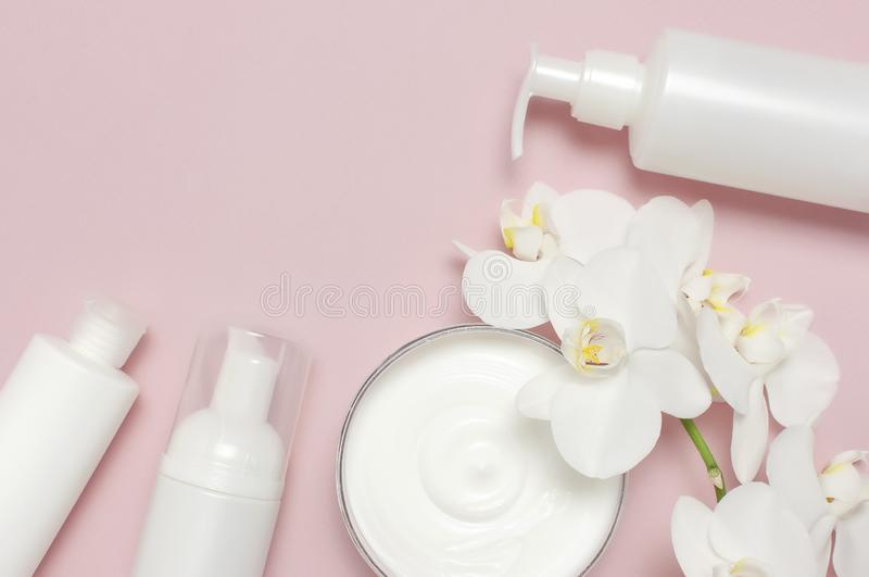 Beauty Spa concept. Opened container with cream, cosmetic bottle containers, white Phalaenopsis orchid flowers on pink background stock images
