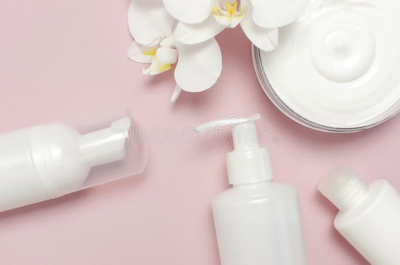 Beauty Spa concept. Opened container with cream, cosmetic bottle containers, white Phalaenopsis orchid flowers on pink background royalty free stock images