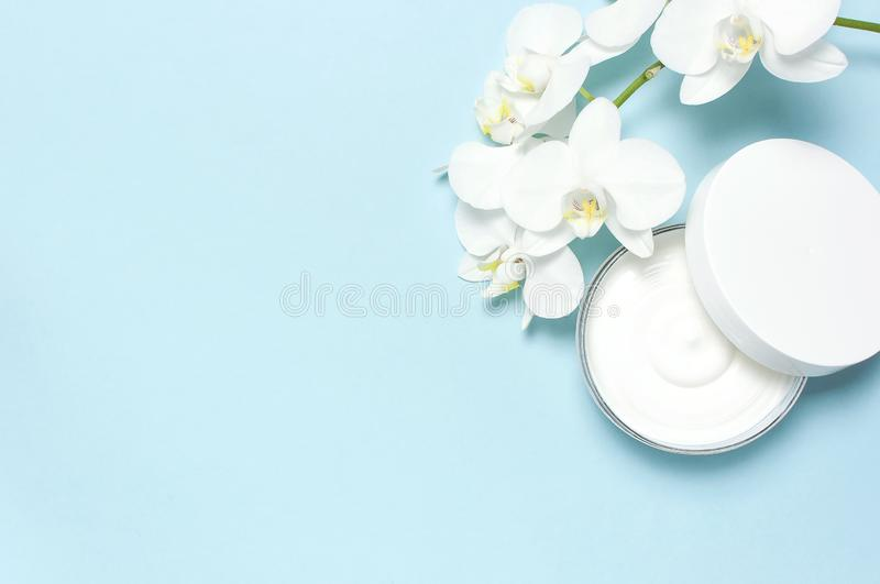 Beauty Spa concept. Opened plastic container with cream and White Phalaenopsis orchid flowers on blue background Flat stock photo