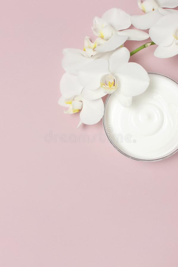 Beauty Spa concept. Opened plastic container with cream and White Phalaenopsis orchid flowers on pink background Flat lay top view royalty free stock images