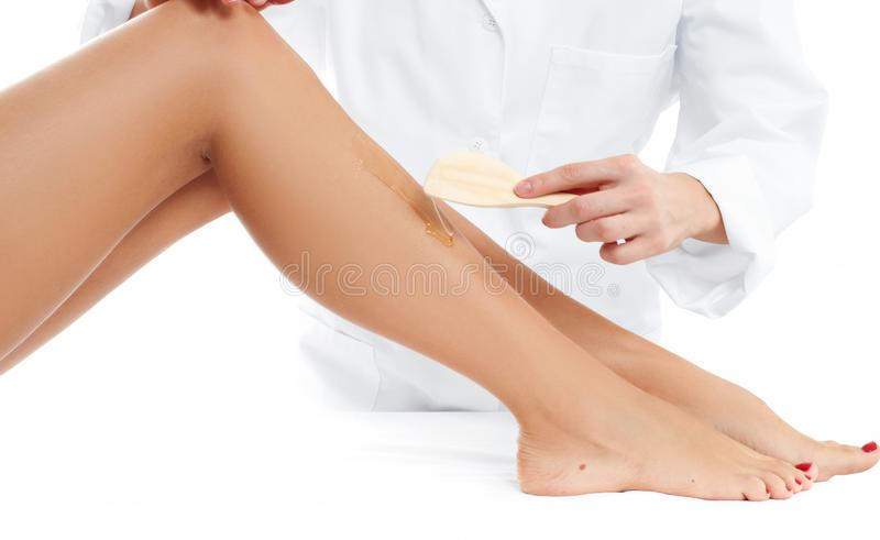 Beauty Spa. Hair removal cosmetology procedure. Beautician waxing female legs. Beauty Spa. Hair removal cosmetology procedure. Beautician waxing a female leg stock image