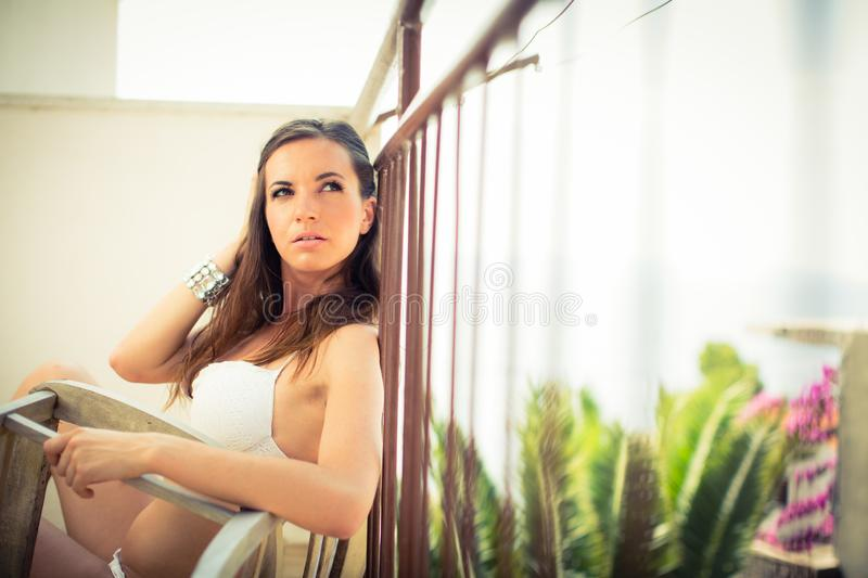Beautiful, young woman by the sea on a balcony of a resort/hotel room stock image