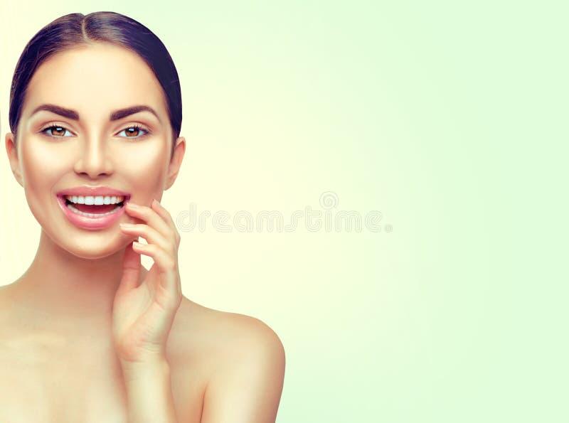 Beauty spa vrouw wat betreft haar gezicht en het glimlachen Het witten van tanden stock afbeelding