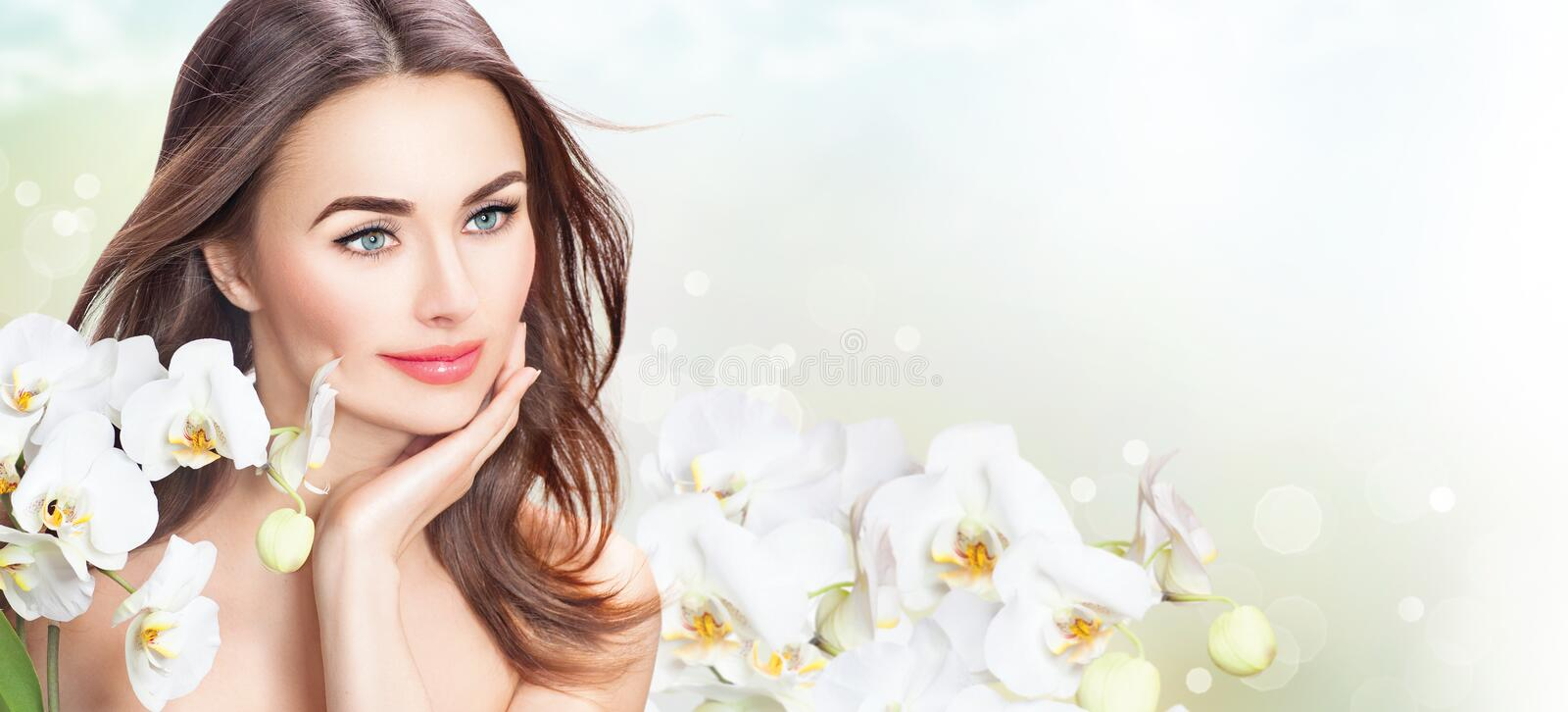 Beauty spa woman with orchid flowers. Beauty woman with orchid flowers. Beautiful spa girl touching her face stock image