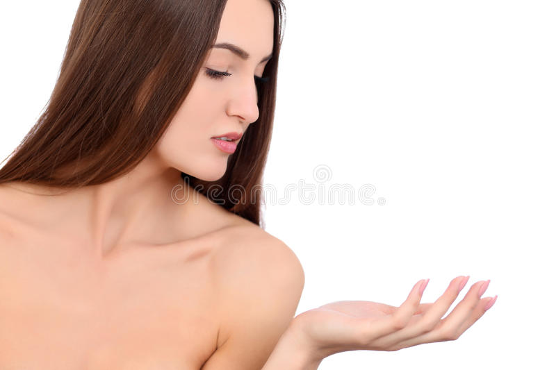 Beauty Spa Woman with perfect skin Portrait. Beautiful Brunette Spa Girl showing empty copy space on the open hand palm. For text. Proposing a product. Gestures royalty free stock photography