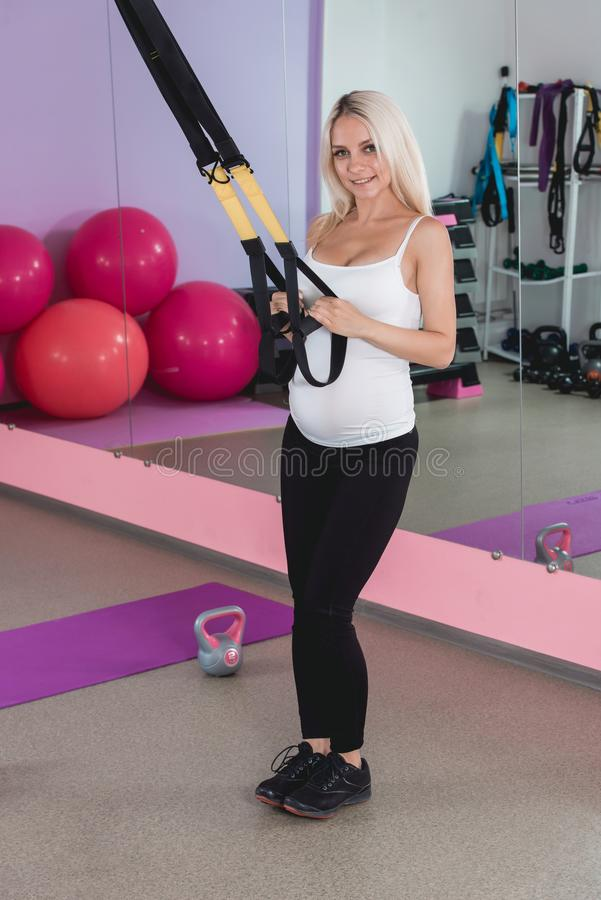 Beauty sporty pregnant woman working out in gym with balls on the background stock images