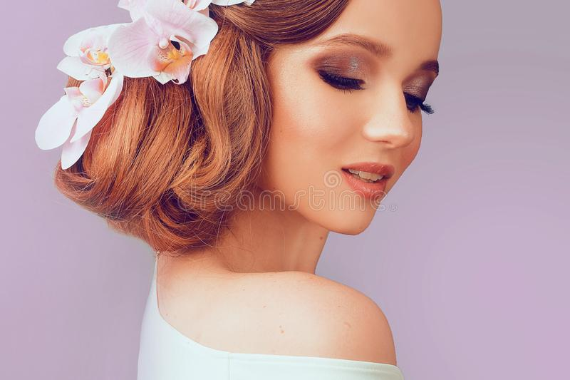 Beauty Summer model girl with colorful Flowers Hair Style. Beautiful Lady with Blooming flowers on her head. Professional Hairstyl. E and wedding Makeup. Summer stock photography