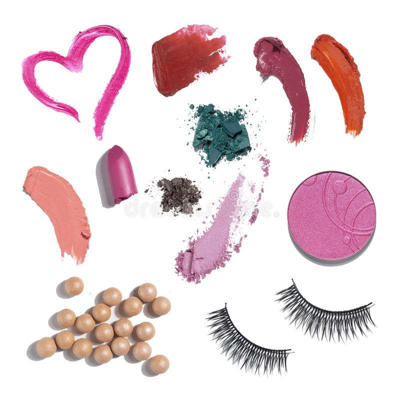 Beauty swatches. Creative concept photo of cosmetics swatches beauty products mix lipstick eyehadow lip gloss blusher ball pearls eyelash extensions on white royalty free stock image