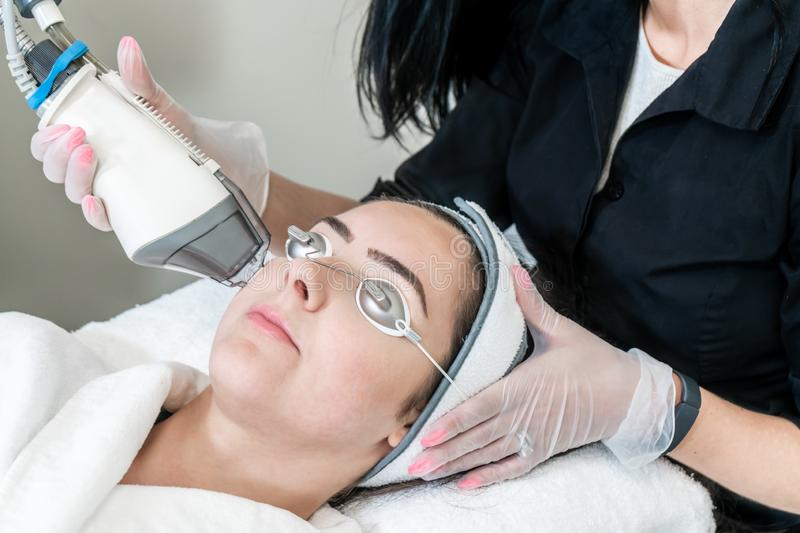 Beauty technician performing skin rejuvenation for removing acne scars, redness and wrinkles on a female patient wearing royalty free stock photo