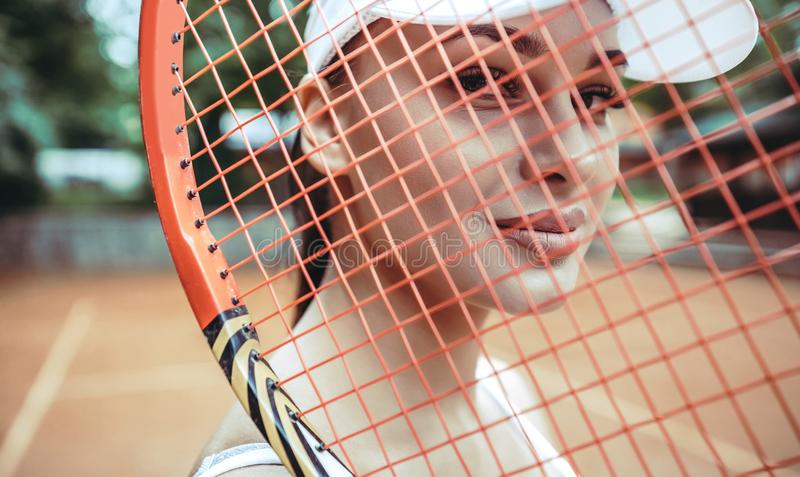 Beauty on tennis court. Portrait of a attractive young caucasian woman looking at camera behind a tennis racket. Sexy tanned royalty free stock image