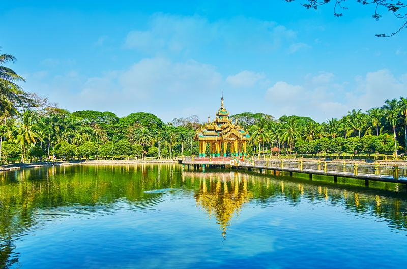 The beauty of Theingottara park, Yangon, Myanmar. The lake shrine in Theingottara park is reflected on the clear water surface with its bridge and greenery stock image