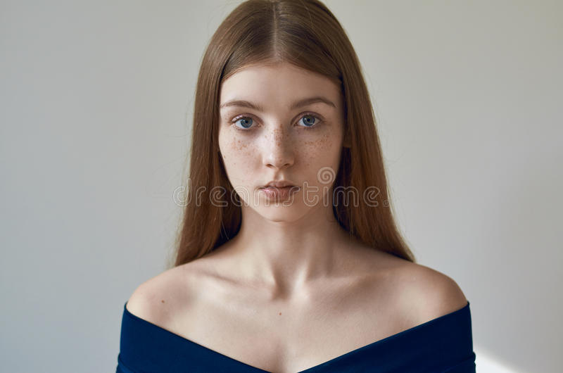 Beauty theme: portrait of a beautiful young girl with freckles on her face and wearing a blue dress on a white background in royalty free stock images