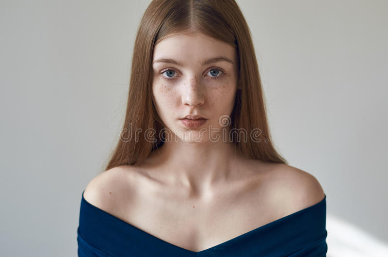 Beauty theme: portrait of a beautiful young girl with freckles on her face and wearing a blue dress on a white background in. Studio shot royalty free stock photo