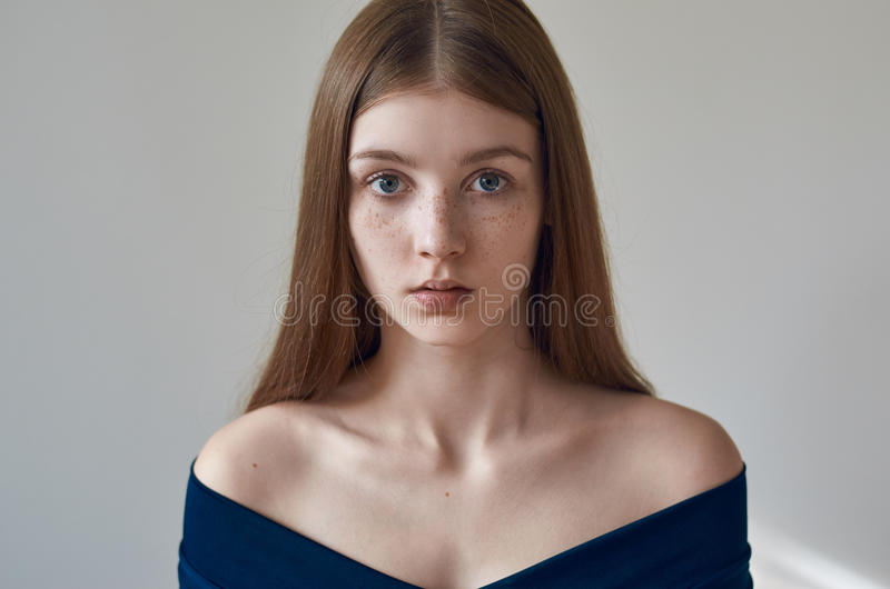 Beauty theme: portrait of a beautiful young girl with freckles on her face and wearing a blue dress on a white background in stock image