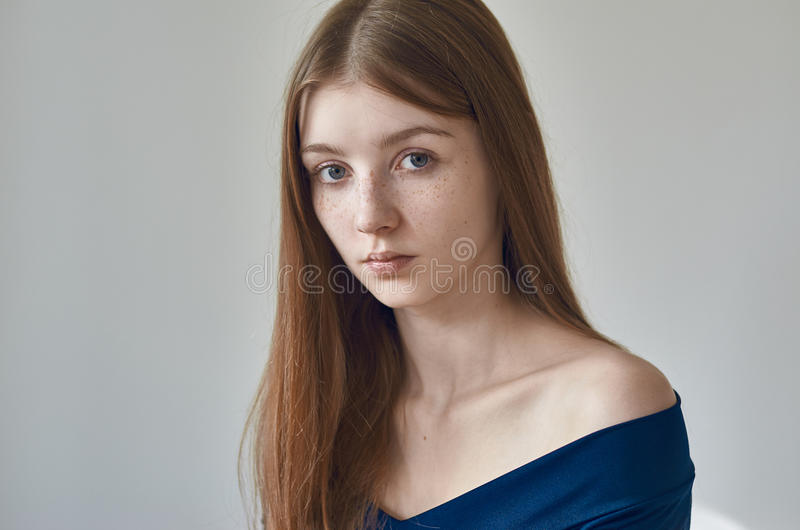 Beauty theme: portrait of a beautiful young girl with freckles on her face and wearing a blue dress on a white background in stock photography