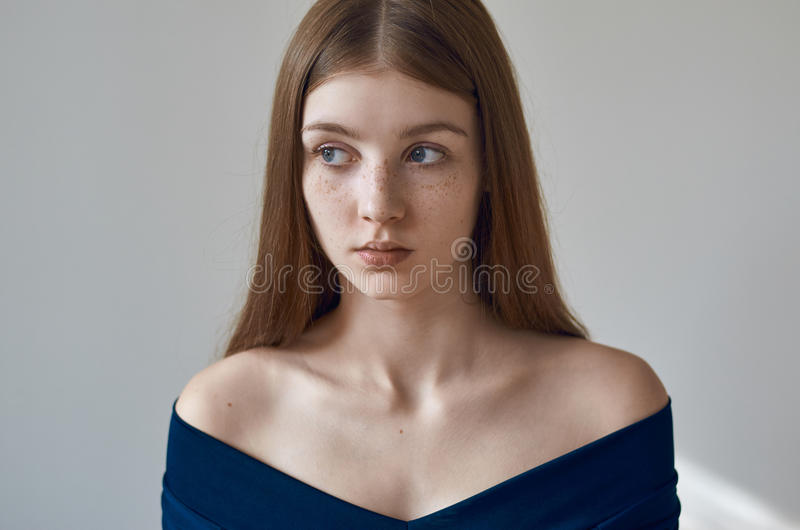 Beauty theme: portrait of a beautiful young girl with freckles on her face and wearing a blue dress on a white background in stock images