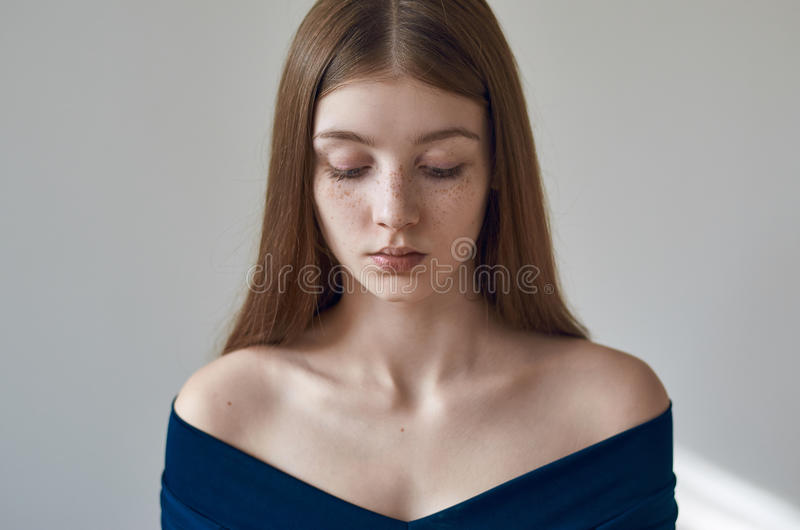 Beauty theme: portrait of a beautiful young girl with freckles on her face and wearing a blue dress on a white background in stock photos