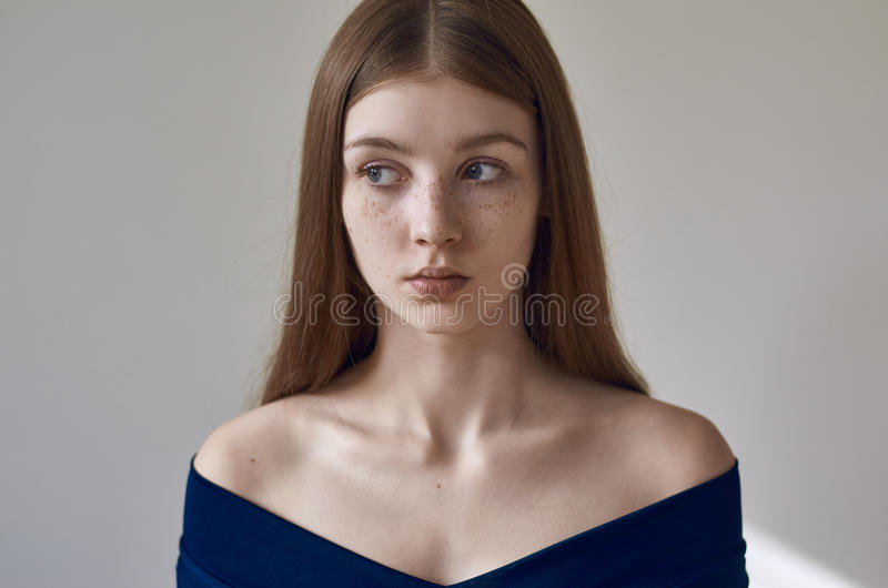 Beauty theme: portrait of a beautiful young girl with freckles on her face and wearing a blue dress on a white background in royalty free stock photo