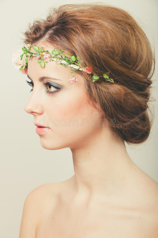 Beauty with tiara of roses. Beautiful blond woman with hair tied back with a tiara of artificial roses royalty free stock photography