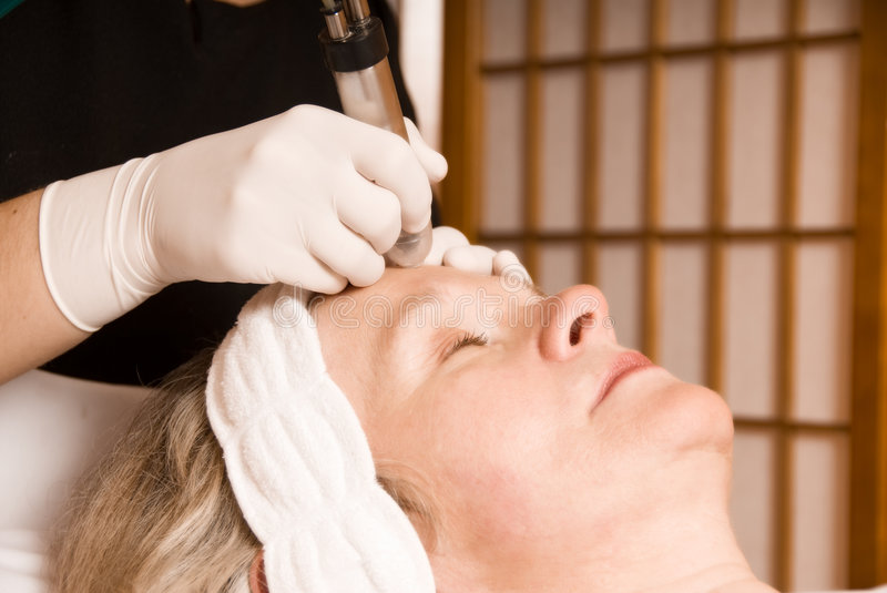 Beauty treatment. Older woman getting electrolysis on he face stock images
