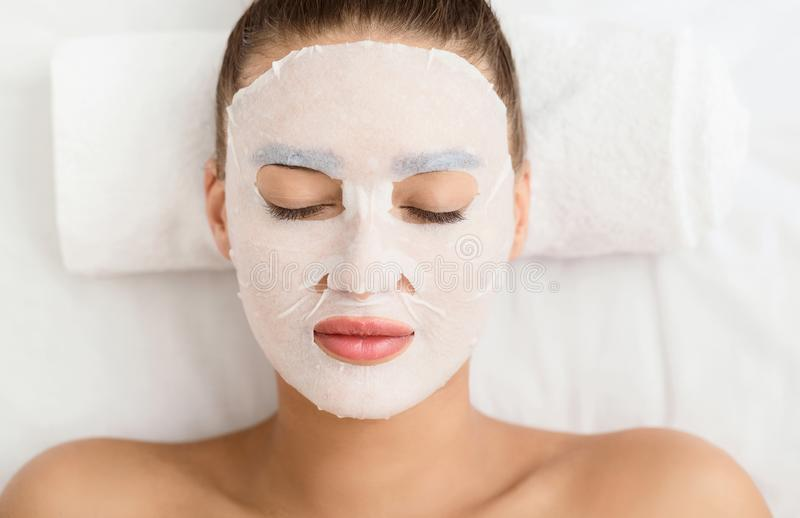 Beauty Treatment Concept. Woman With Facial Sheet Mask. At Spa Salon, Top View royalty free stock photo