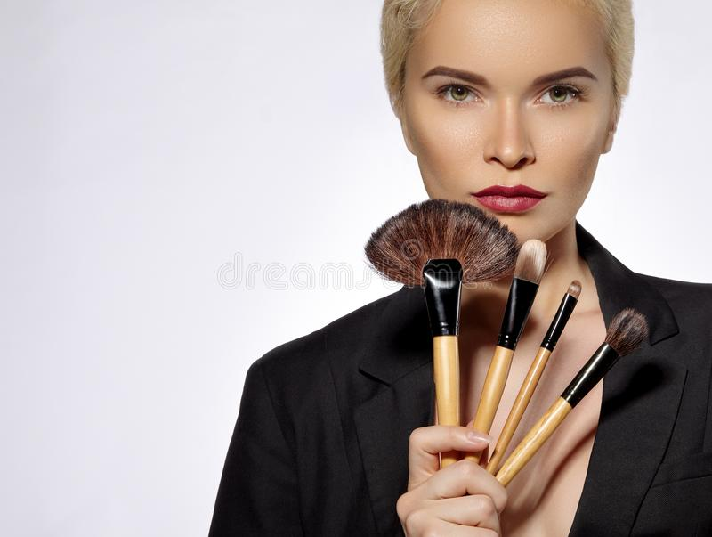 Beauty Treatment. Girl with Makeup Brushes. Fashion Make-up for Woman. Makeover. Make-up Artist Applying Visage royalty free stock image