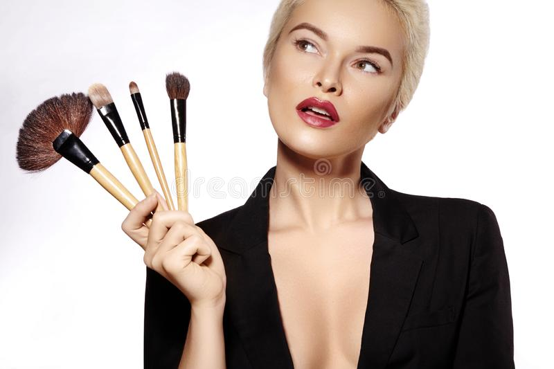 Beauty Treatment. Girl with Makeup Brushes. Fashion Make-up for Woman. Makeover. Make-up Artist Applying Visage. On white background royalty free stock image