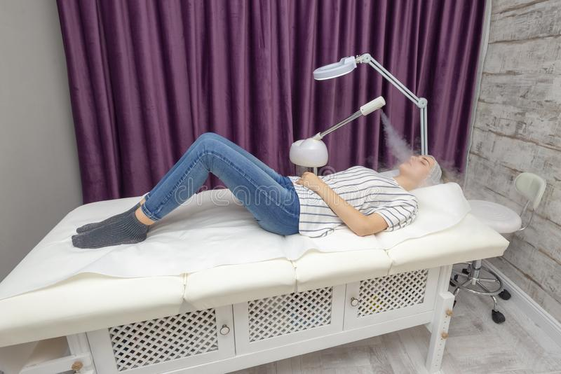 Beauty treatment of young female face, ozone facial steamer. Beauty treatment stock images