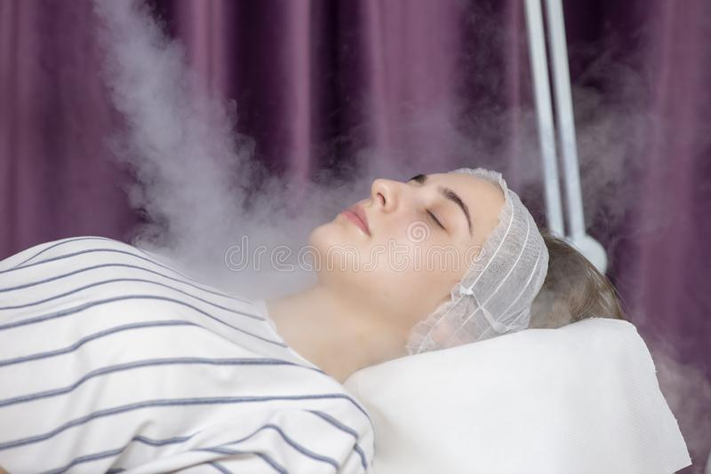 Beauty treatment of young female face, ozone facial steamer. Beauty treatment royalty free stock image