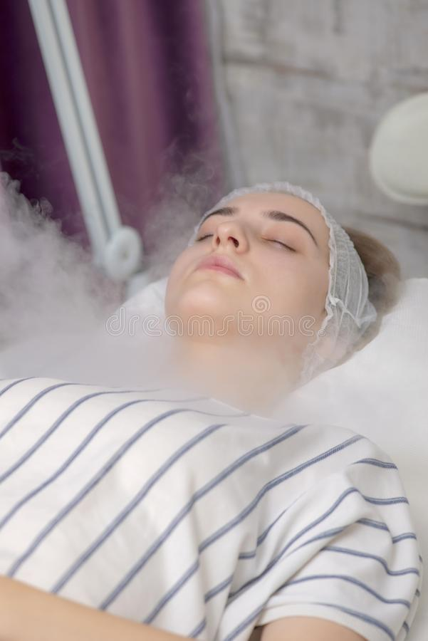 Beauty treatment of young female face, ozone facial steamer. Beauty treatment stock photo