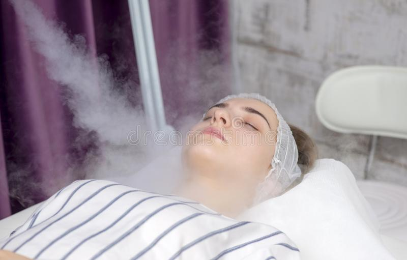 Beauty treatment of young female face, ozone facial steamer. Beauty treatment stock photography
