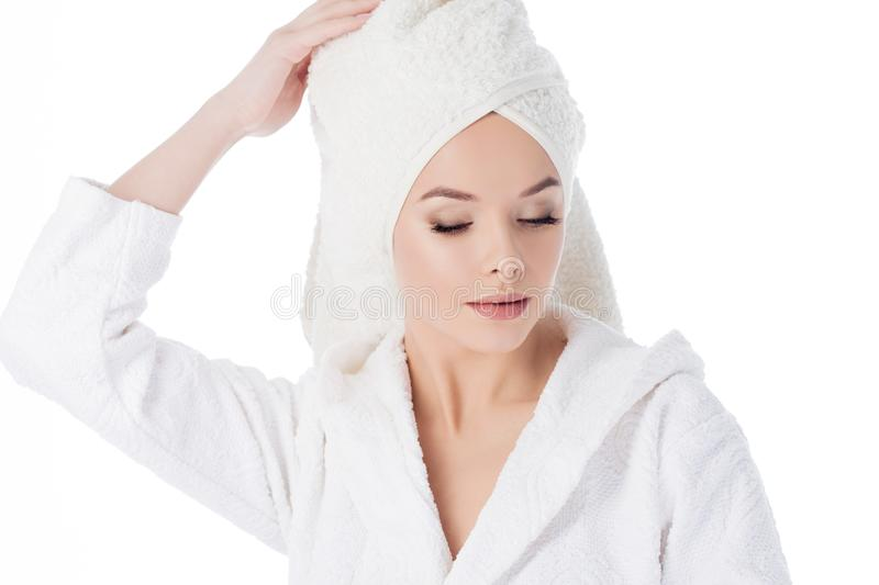 Beauty treatments after the bath. Portrait of a young beautiful woman in a Terry robe and with a towel on her head. stock photography