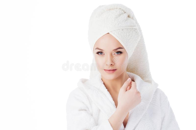 Beauty treatments after the bath. Portrait of a young beautiful woman in a Terry robe and with a towel on her head. stock photos