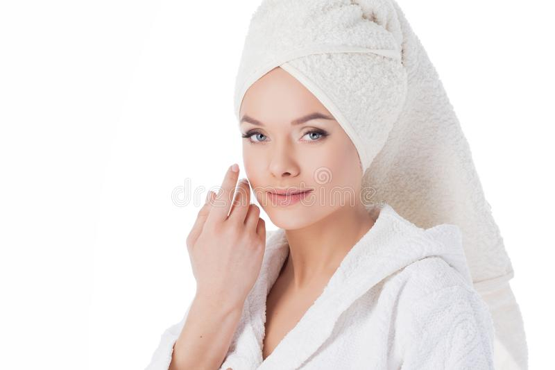 Beauty treatments after the bath. Portrait of a young beautiful woman in a Terry robe and with a towel on her head. stock images