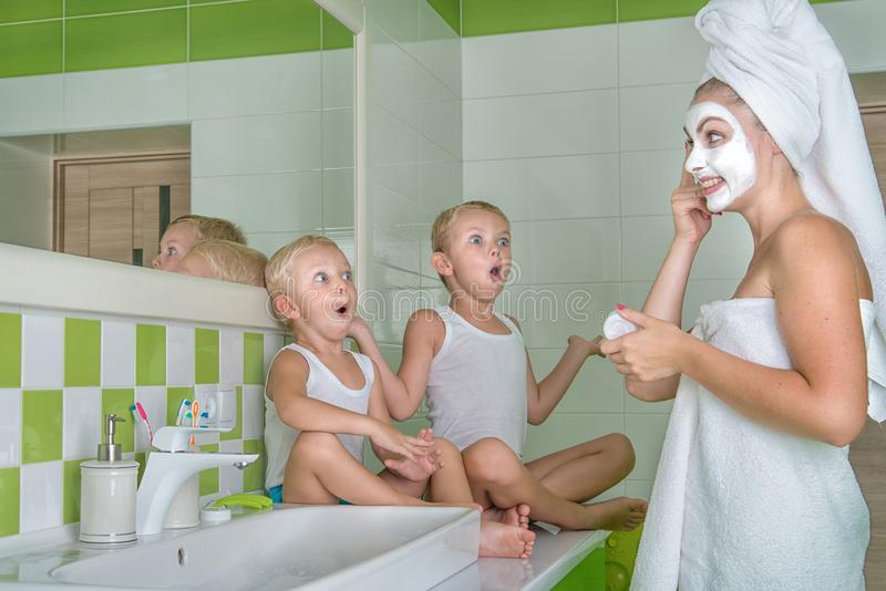 A young woman make a face mask.Children watching the mother,surprised faces.Beauty treatments for the skin. Beauty treatments for the skin.A young women make royalty free stock photography