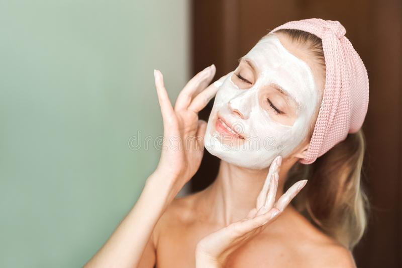 Beauty Treatments. Young woman is applying a mask, cream on her face close-up. Facial skin care portrait of a beautiful girl with royalty free stock photos