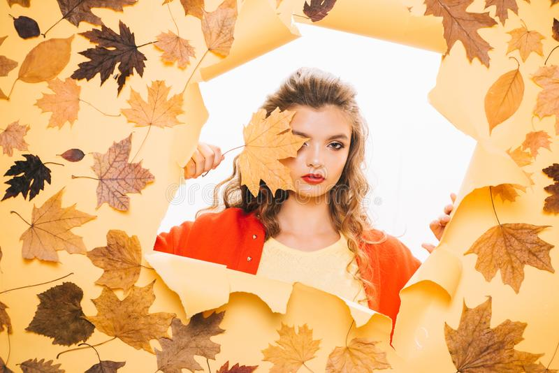 Beauty trends. Makeup girl peek through torn paper. Pretty girl cover face with autumn leaf. Young woman look out of. Hole. Fashion model with decorative fall royalty free stock image