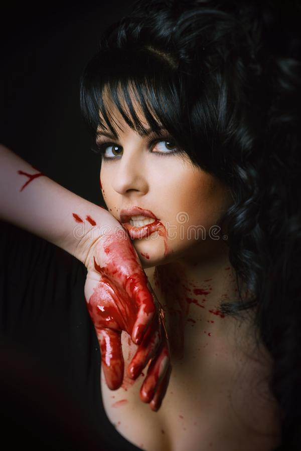Beauty vampire girl. With blood on face on black background stock photo