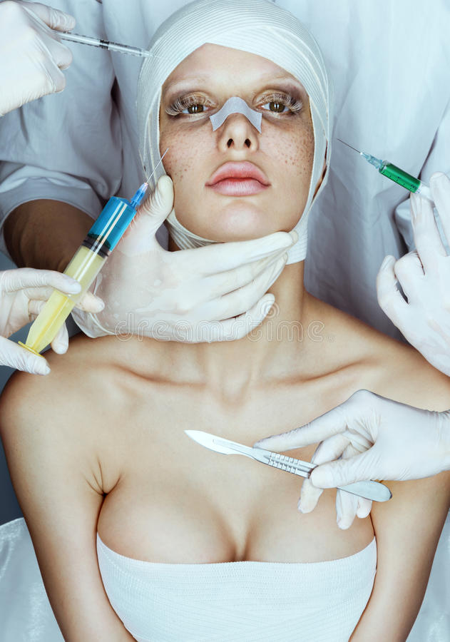 Beauty victim wrapped in medical bandages while doctors with syringes and scalpels near her face. Beauty concept royalty free stock photography