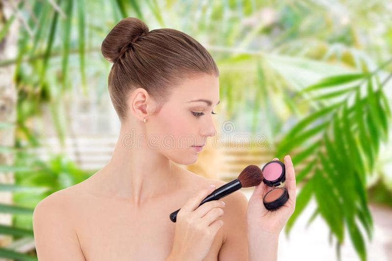 Portrait of young beautiful woman with make up brush and rouge over summer background royalty free stock images