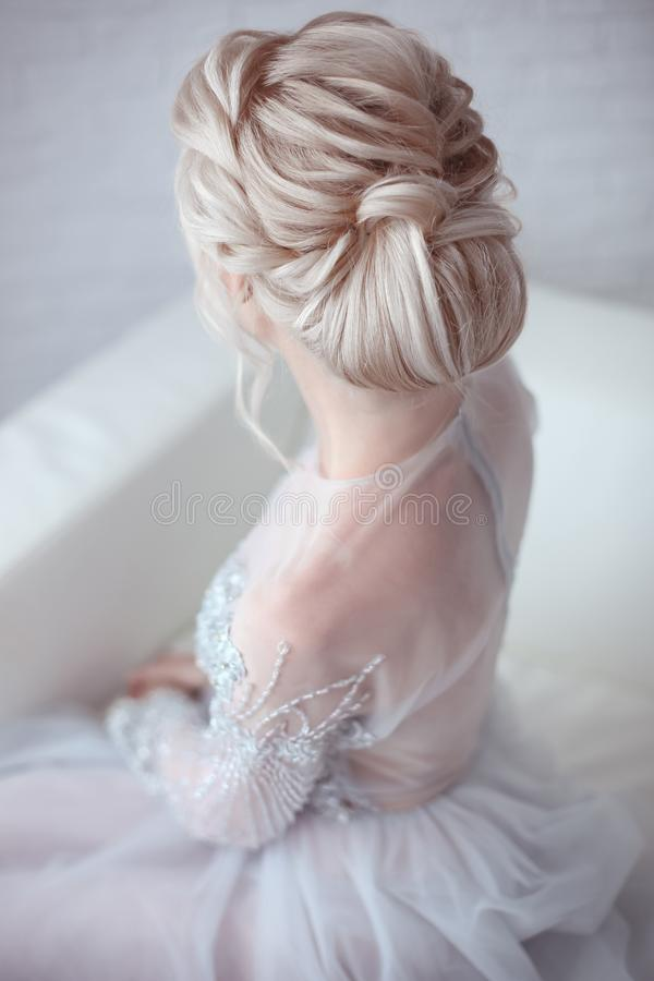 Beauty wedding hairstyle. Bride. Blond girl with curly hair styling. Back view of elegant lady in bridal dress. stock images