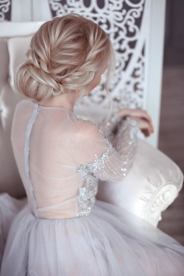 Beauty wedding hairstyle. Bride. Blond girl with curly hair styling. Back view of elegant lady in bridal dress. stock image
