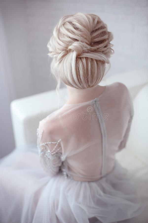 Beauty wedding hairstyle. Bride. Blond girl with curly hair styling. Back view of elegant lady in bridal dress. stock photos