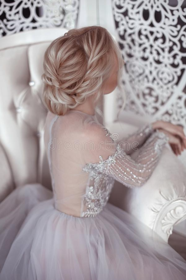 Beauty wedding hairstyle. Bride. Blond girl with curly hair styling. Back view of elegant lady in bridal dress. stock photo