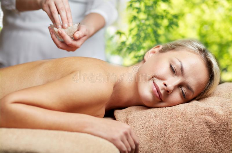 Woman having salt massage in spa stock images